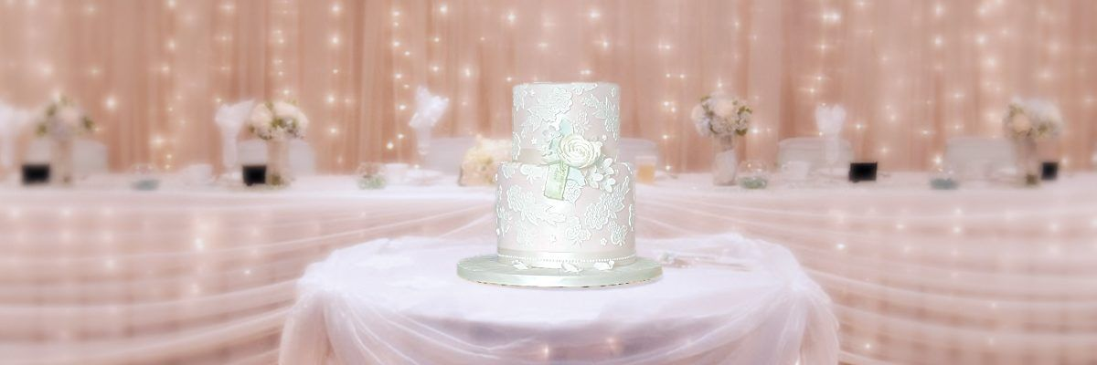 Pink wedding cake with white lace and flower