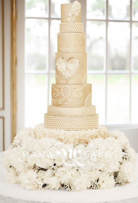 Eight tiered wedding cake decorated with champagne and ivory on flower stand by Mama Cakes Cumbria