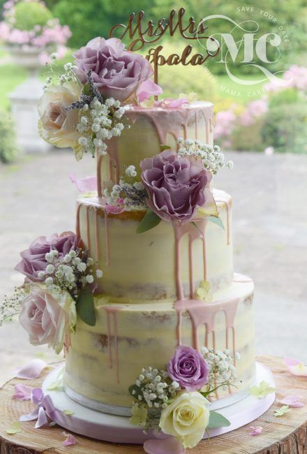 Semi-naked white chocolate wedding cake with a mix of roses and delicate gypsophilas by Mama Cakes Cumbria